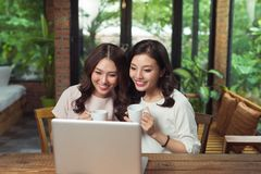 Young female friends surfing the internet together on a laptop Stock Photos