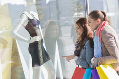 Young female friends window shopping stock images