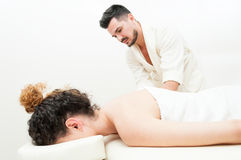 Young female is getting a body massage by handsome man Royalty Free Stock Images