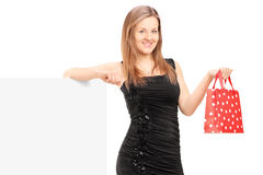 Young female with a gift bag standing next to a blank panel Royalty Free Stock Image