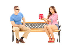 Young female giving a gift box to her boyfriend, on a bench Royalty Free Stock Photography