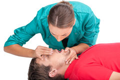 Young female giving patient CPR. Royalty Free Stock Images