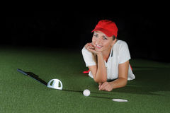 Young female golf player on artificial field at the mini golf club. The ball, the golf club and hole course are near a girl. Mini golf inside interior Stock Images