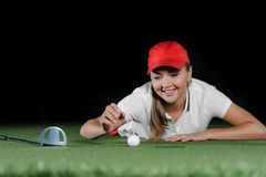 Young female golf player on artificial field at the mini golf club. The ball, the golf club and hole course are near a girl. Mini golf inside interior Stock Photography