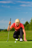 Young female golf player on course aiming for put. Young female golf player on course aiming for her put Royalty Free Stock Photo