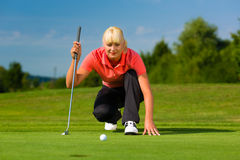 Young female golf player on course aiming for put. Young female golf player on course aiming for her put Royalty Free Stock Photography