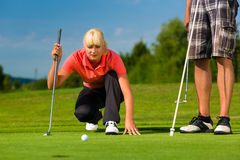 Young sportive couple playing golf on a course. Young female golf player on course putting, she aiming for her put shot Royalty Free Stock Image