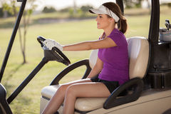 Young female golfer driving a cart Stock Photo