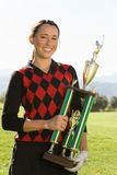 Young Female Golfer Holding Trophy Stock Image