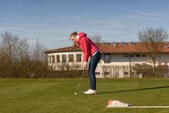 Young Female Golfer Putting Ball Towards Hole. Young Female Golfer Wearing Casual Jacket and Jeans Putting Ball Towards the Hole Stock Image