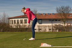 Young Female Golfer Putting Ball Towards Hole. Young Female Golfer Wearing Casual Jacket and Jeans Putting Ball Towards the Hole Royalty Free Stock Photo