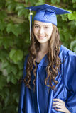 A young female graduate with blue cap and gown. Stock Photography