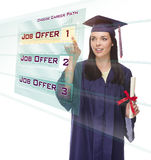 Young Female Graduate Choosing Job Button on Translucent Panel. Attractive Young Mixed Race Female Graduate in Cap and Gown Choosing Job Offer 1 Button on Royalty Free Stock Photo