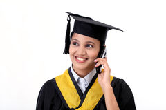 Young female graduation student talking on mobile Stock Photography