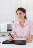 Young female graphic artist sitting at des working with tablet. Stock Photography