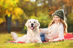 Young female on a grass with her labrador retriever dog in autum Royalty Free Stock Photography