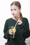 Young Female in Green Jersey with Glass of Soft Drink Royalty Free Stock Images