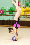 Young female gymnast doing crafty trick with ball Stock Photography