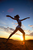 Young female gymnast exercising at sunrise. On a city beach royalty free stock photo