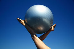 Young female gymnast with yoga ball held between legs. Young female gymnast with a yoga ball raised in the sky between her slender legs royalty free stock photos