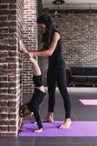 Young female gymnastics teacher assisting the child girl doing handstand against wall.  stock image