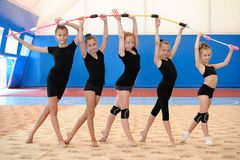 Young female gymnasts making bow with Indian clubs Royalty Free Stock Images