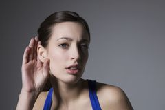 Young Female With Hand Behind Ear Royalty Free Stock Photography