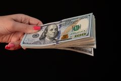 Young female hand count dollar bills on black background, closeup royalty free stock image