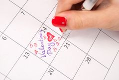 Women hand with pencil drawing hearts shape and words in calendar for Valentines day. Young female hand with pencil drawing hearts shape and words in calendar Stock Images