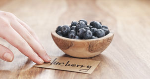 Young female hand putting paper card near bowl of blueberries on table Royalty Free Stock Photo
