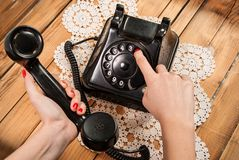 Woman hand dialing number on old phone on lace tablecloths and wooden background. Young female hand with red nails polish and sweater holding old phone on wooden Royalty Free Stock Images