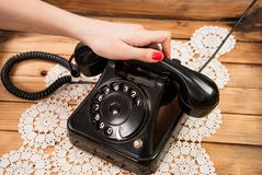 Girl hand holding old telephone headset on lace tablecloths and wooden background royalty free stock photo