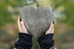 2 young female hands with black fingernails holding a wooden heart covered with lichen as a symbol of friendship, love stock photos