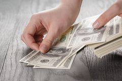 Young female hands count dollar bills on wood Stock Images