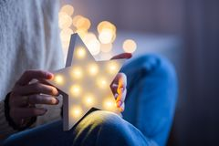 Young female hands holding glowing white LED star on bokeh background indoor. Young female hands holding glowing white LED star on warm bokeh background indoor stock images