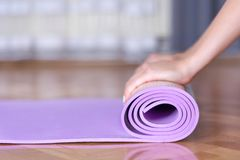 Young female hands roll yoga or fitness purple mat on parquet floor. Young girl hands roll yoga or fitness purple mat on parquet floor in the house. Sport and stock photography