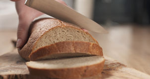 Young female hands slicing rye wheat rustic bread on cutting board Stock Image