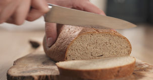 Young female hands slicing rye wheat rustic bread on cutting board Royalty Free Stock Photo