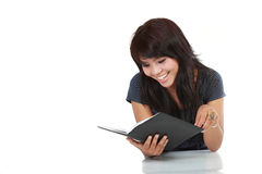 Young female happily reading book Royalty Free Stock Photography