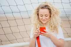 Young female has curly hair holds modern smart phone, downloads photos from social networks, poses against tennis net background,. Uses free internet. Beautiful Royalty Free Stock Image