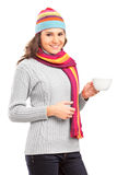 Young female with hat and scarf holding a cup of tea Stock Photo