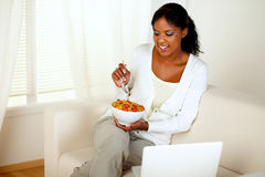 Young female having breakfast and using laptop Royalty Free Stock Photo