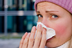Young female having a cold. Young female with red cheeks cleaning her nose with a tissue Royalty Free Stock Photo