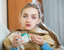 Young female having quinsy and fever and staying in couch. Portrait of female with quinsy and fever under blanket Royalty Free Stock Photo