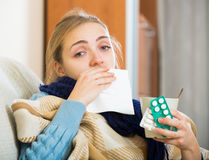 Young female having quinsy and fever and staying in couch. Portrait of female with quinsy and fever under blanket Stock Photography