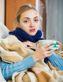 Young female having quinsy and fever and staying in couch. Portrait of female with quinsy and fever under blanket Stock Images