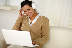 Young female with headphone reading laptop screen Royalty Free Stock Image