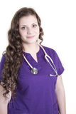 Young Female Health Care Worker with Purple Scrubs. A smiling twenty something health care worker with purple scrubs and pink stethoscope around her neck Stock Photography