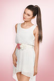 Young female with healthy shining brown hairs. Put in pony tail. White dress Royalty Free Stock Photography