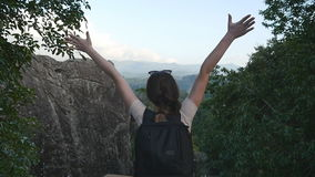 Young female hiker with backpack reaching up top of mountain and raised hands. Woman tourist standing on the edge of stock video